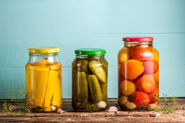 Gläser mit essiggurken von zucchini, gurken, tomaten auf einem blauen, hölzernen hintergrund.