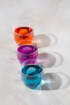 Gläser mit farbiger flüssigkeit auf hellem marmorhintergrund
