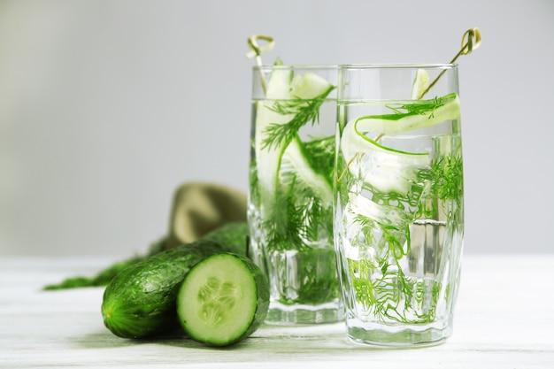 Gläser mit frischem bio-gurkenwasser auf holztisch, auf grau
