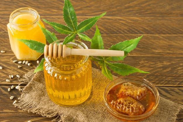 Gläser mit frischem cbd-honig mit honiglöffel auf holztisch, nahaufnahme mit hanfblättern.
