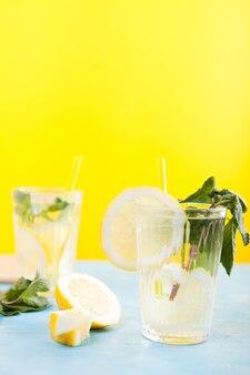 Gläser mit frischem hausgemachtem detox-wasser mit zitronen auf gelbem hintergrund auf blauem tisch sitzend