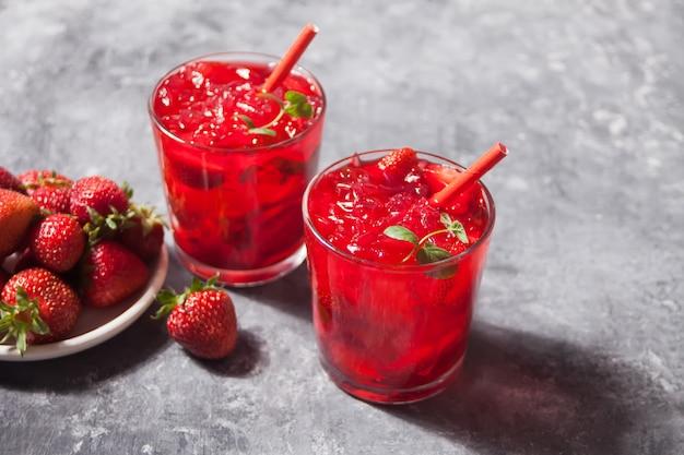 Gläser mit frischem selbst gemachtem erdbeersüßem eistee oder cocktail, limonade mit minze. erfrischendes kaltes getränk. sommerfest.