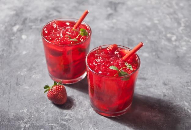 Gläser mit frischem selbst gemachtem erdbeersüßem eistee oder cocktail, limonade mit minze.