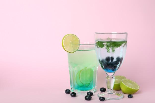 Gläser mit frischen sommercocktails und zutaten auf rosa hintergrund
