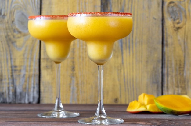 Gläser mit gefrorenen mango-margarita-cocktails, garniert mit paprikasalzrand
