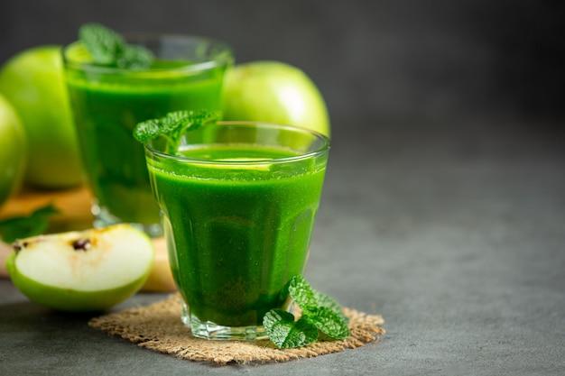 Gläser mit gesundem smoothie aus grünem apfel neben frische grüne äpfel