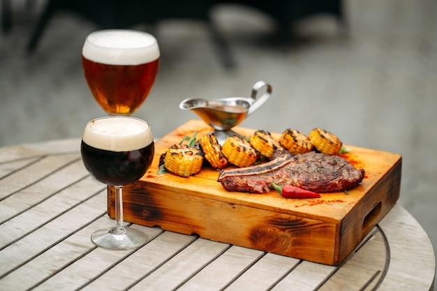 Gläser mit goldenem und dunklem bier mit gegrilltem rindersteak in einem holztablett