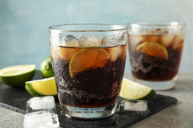Gläser mit kalter cola und zitrusfrüchten auf grauem tisch, platz für text