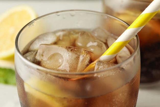 Gläser mit kalter cola und zitrusfrüchten auf weißem zementhintergrund