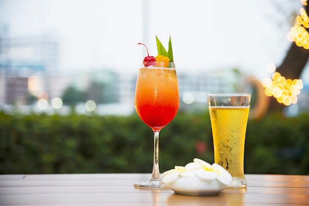Gläser mit kühlem bier und mai tai oder mai thai weltweit bevorzugen einen cocktail in der dämmerung
