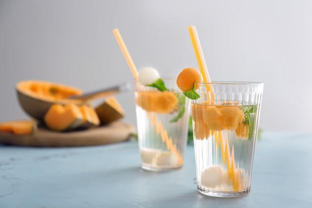Gläser mit leckeren cocktails mit melonenkugeln auf leuchttisch