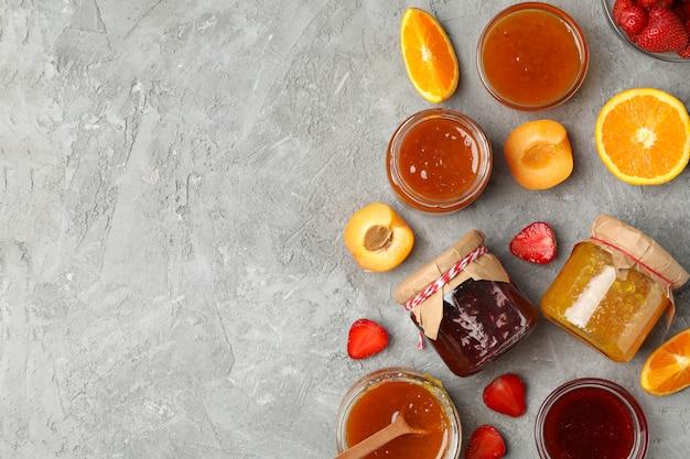 Gläser mit marmelade und zutaten auf grauer draufsicht