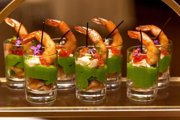 Gläser mit meeresfrüchten und grünen nudeln vorspeisen bankettplatte für veranstaltungen und buffet.