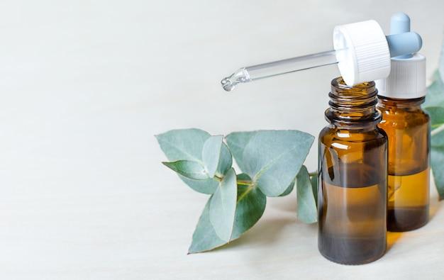 Gläser mit nasentropfen und einem zweig eukalyptus.