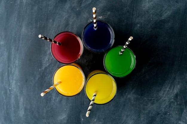 Gläser mit rotem gelbgrünem orange und purpurrotem frischem smoothie auf dunkle oberflächen