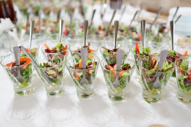 Gläser mit salat auf weißem tisch serviert