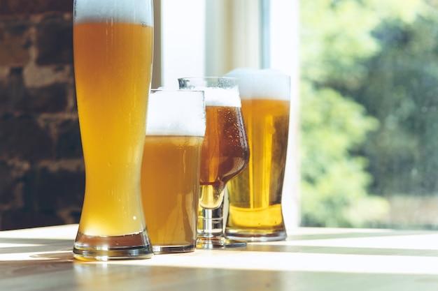 Gläser mit verschiedenen arten von hellem bier im sonnenlicht.