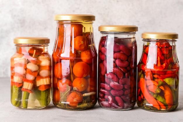 Gläser mit verschiedenen gemüsekonserven und bohnen auf grauem tisch