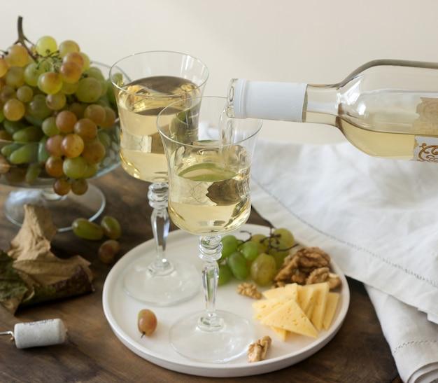 Gläser mit weißwein und eine flasche wein mit einem snack - käse, walnüssen und trauben. rustikaler stil.
