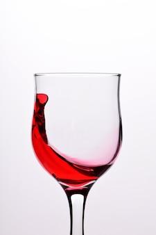 Gläser mit wellen prallen vom rotwein auf einem weißen hintergrund