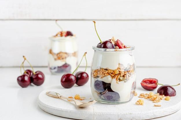 Gläser müsli mit joghurt und süßkirschen auf weißem holzbrett.