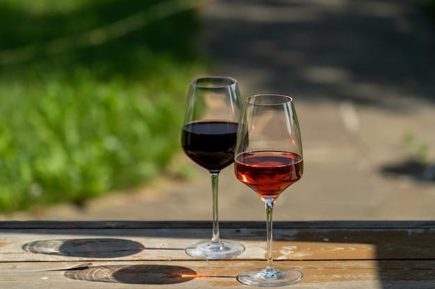 Gläser rot- und rosawein mit schatten über grünem gartenhintergrund.