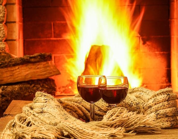 Gläser rotwein gegen gemütlichen kaminhintergrund, winterferien.