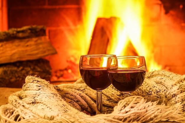 Gläser rotwein vor gemütlichem kaminhintergrund, winterferien.