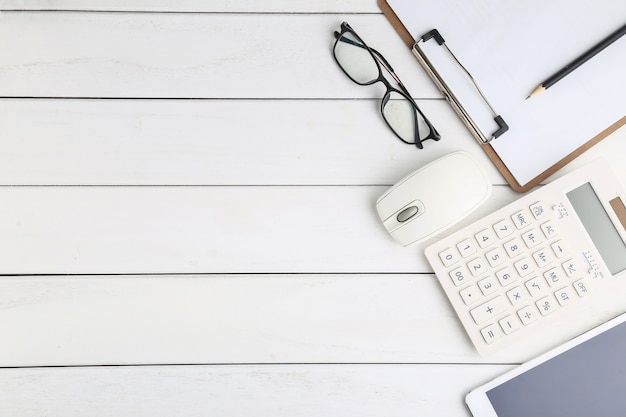 Gläser, taschenrechner und tablette auf weissem schreibtisch