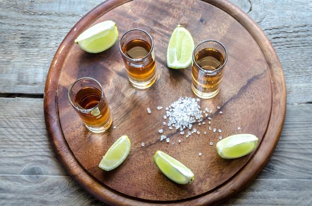 Gläser tequila auf dem holzbrett