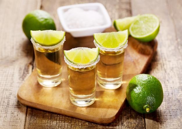 Gläser tequila mit limette auf holztisch