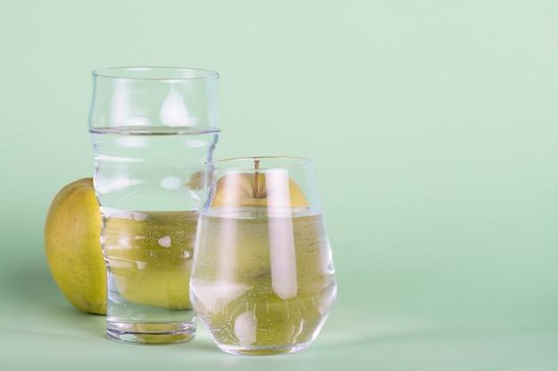 Gläser und apfel auf grünem hintergrund