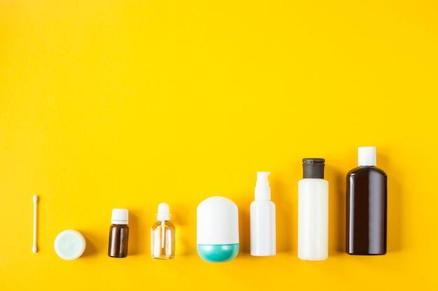 Gläser und behälter mit kosmetischen produkten sind auf gelbem grund hintereinander angeordnet.