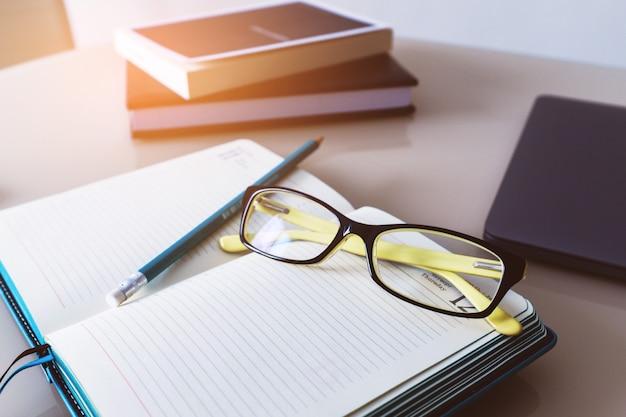 Gläser und ein bleistift auf einem notizbuch, ein tagebuch. geschäftliche ausbildung