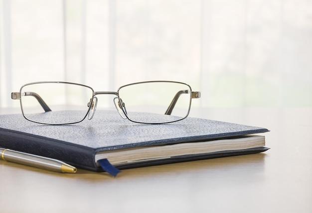Gläser und ein buch auf dem schreibtisch
