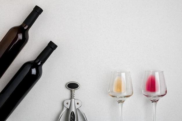 Gläser und flaschen rot- und weißwein auf weißem hintergrund aus der draufsicht