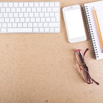 Gläser und gadgets in der nähe von bleistift und notizbuch