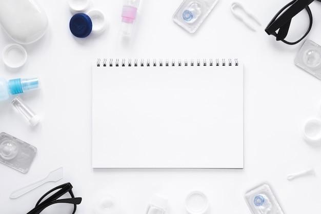 Gläser und optische gegenstände mit notizbuchmodell auf weißem hintergrund