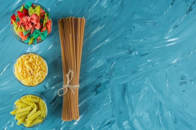 Gläser verschiedener trockener ungekochter nudeln auf blauem hintergrund.