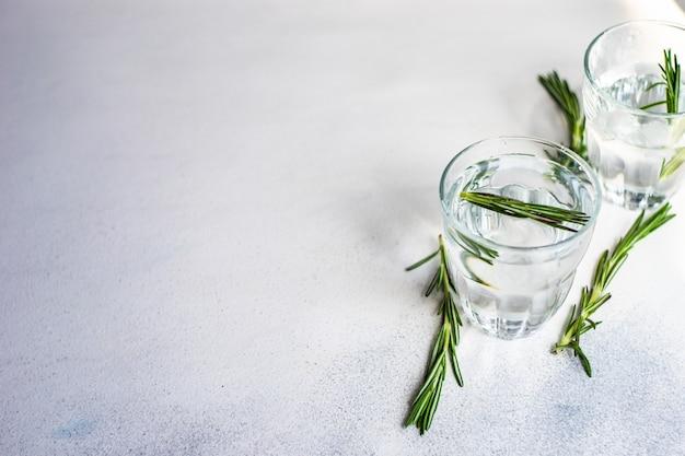 Gläser wasser mit eis und rosmarin auf weißem betontisch