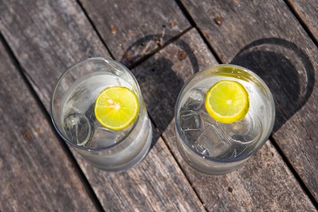 Gläser wasser mit zitrone auf hölzernem
