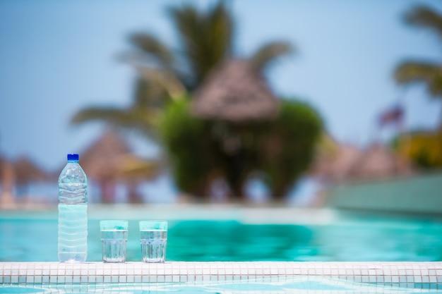 Gläser wasser und swimmingpool des flaschenhintergrundes