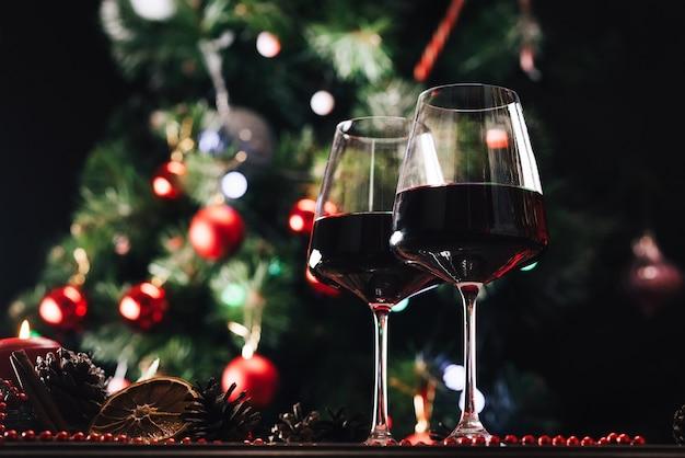 Gläser wein auf dem hintergrund eines geschmückten weihnachtsbaums. neujahr