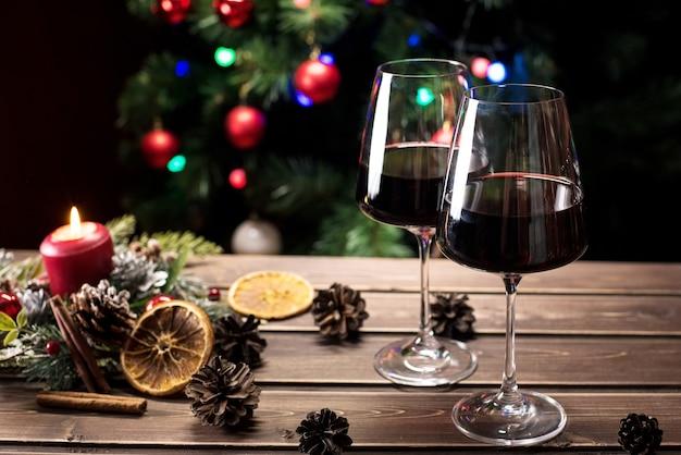 Gläser wein auf dem hintergrund eines geschmückten weihnachtsbaums. neujahrsstimmung