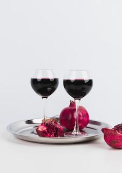 Gläser wein mit granatapfel auf einem tellersegment