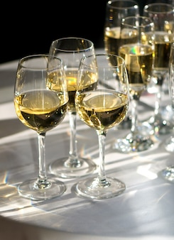 Gläser weißwein beleuchtet von sonnenstrahlen