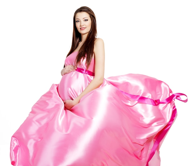 Glamour ans stilvolle schwangere schöne frau im rosa blasenden kleid - weißer raum