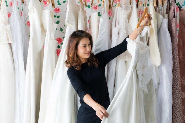 Glamour-asiatische brauthochzeitsgeschäftsbesitzerin, die in ihrem studio arbeitet, kleidung und brautkleid mit lächeln und glück auswählt und überprüft. designer- und unternehmerkonzept.