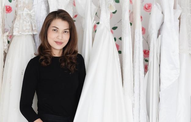 Glamour-asiatische brauthochzeitsgeschäftsbesitzerin, die in ihrem studio arbeitet und zwischen brautkleidern mit lächeln und glück steht. designer- und unternehmerkonzept.