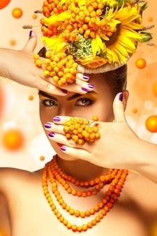 Glamour erwachsenes mädchen mit schönem make-up und rowan-accessoires verbirgt das gesicht hinter den händen